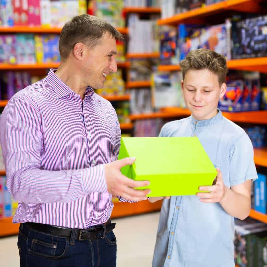 dad handing gift box to son to represent gifts for 14 year old boys